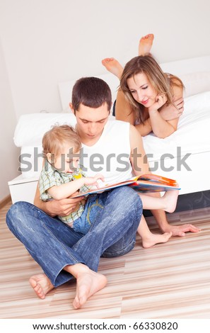 happy family, mother ,father and their baby read a book at home - stock photo