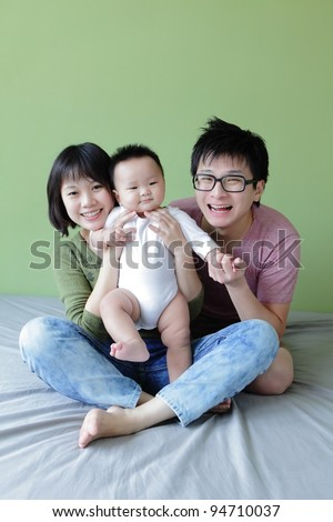 happy family, mother ,father and their baby with green background, model are asian family - stock photo