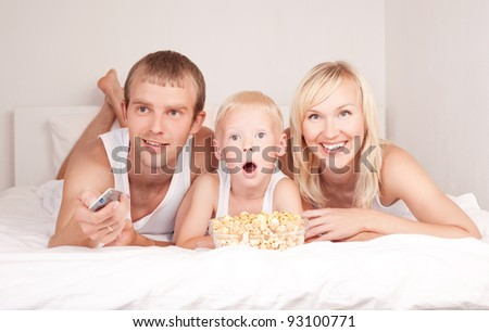 happy family: mother ,father and their son watching TV and eating popcorn on the bed at home - stock photo