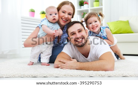 happy family mother, father and two children playing and cuddling at home on floor - stock photo