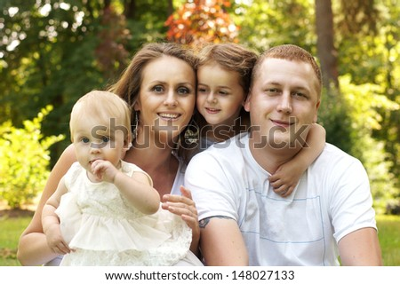 happy family. mother. father and two daughters hugging each other              - stock photo
