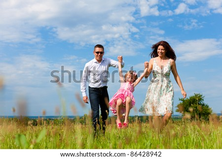 Happy family - mother, father, child - running over a green meadow in summer - stock photo