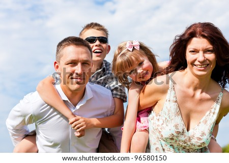 Happy family - mother, father, children - standing on a meadow in summer under blue sky - stock photo