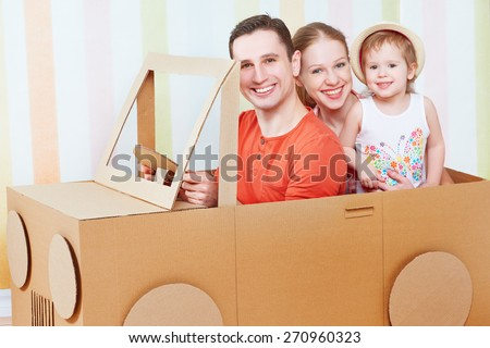 Happy family mother, father, daughter ride on toy car made of cardboard on vacation - stock photo