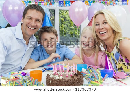 Happy family, mother, father, son & daughter celebrating a children's birthday party with the cake - stock photo