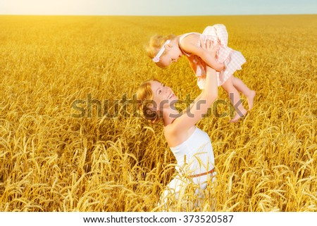 happy family mother throws the baby into the sky in a wheat field in summer - stock photo