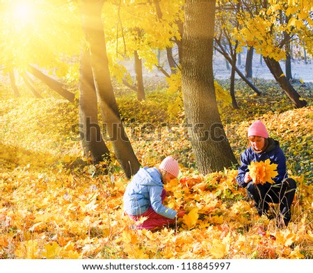 Happy family (mother with daughter) in golden evening maple autumn park and sunshine behind the tree foliage - stock photo