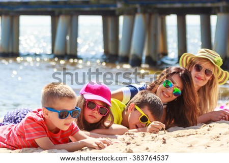 Happy family mothers, daughter and sons sunbathing on beach sand. People parents and children kids at sea. Summer vacation holidays relax and happiness. - stock photo