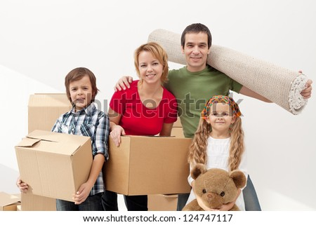 Happy family moving into a new home carrying their stuff - stock photo