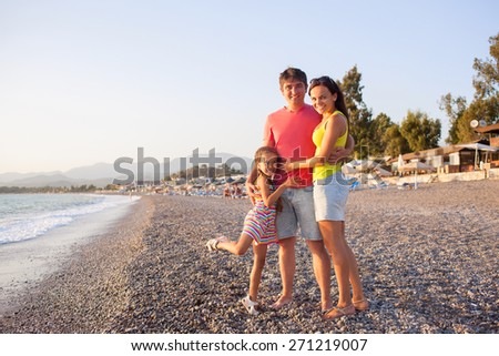 Happy family mum, dad and kid daughter playing and posing on the beach during sunset - stock photo
