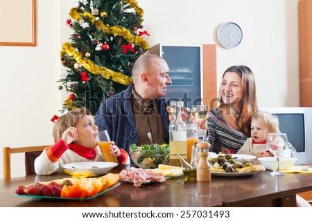 happy family near Christmas tree over celebratory table at home interior - stock photo