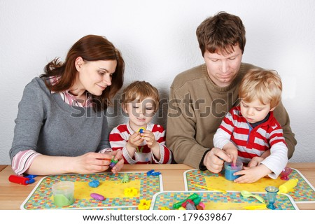 Happy family of a four: mother, father and two sibling boys having fun with modeling clay at home - stock photo