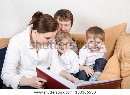 Happy family of a four watching old photos at home. In blue jeans and white shirts - stock photo