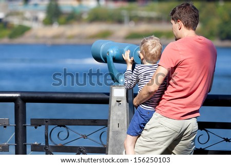 happy family of father and his son using seaside binoculars together - stock photo