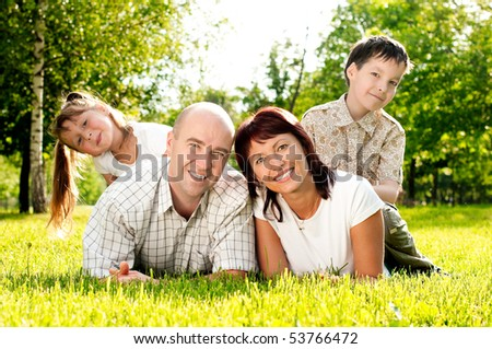 happy family of father and mother and their kids: brother and sister, on grass in park. All smiling and looking in camera - stock photo