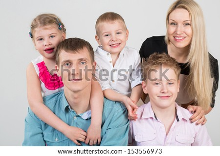 Happy family of five people, daughter hugging father in the studio - stock photo