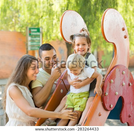 Happy family of four at children's playground. Focus on man