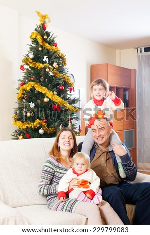 Happy family of four celebrating Christmas on sofa - stock photo