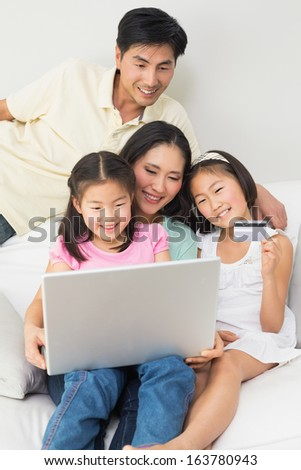 Happy family of four doing online shopping through laptop and credit card at home - stock photo