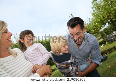 Happy family of four having fun outside - stock photo
