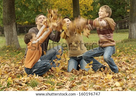 Happy family of four having fun together in the park in autumn - stock photo