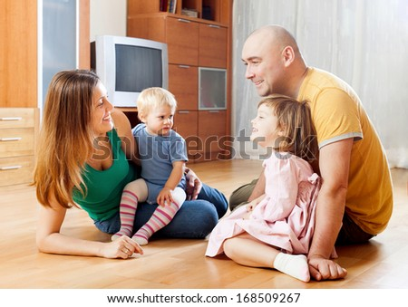 Happy family of four in home - stock photo