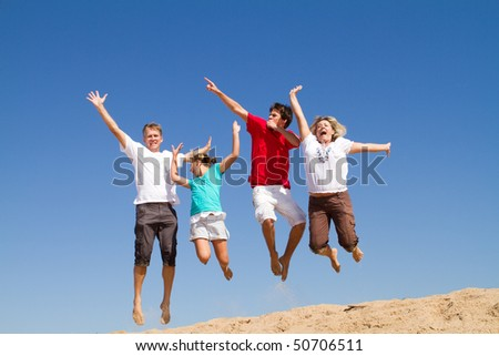 happy family of four jumping with bright blue sky at background - stock photo