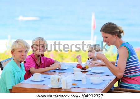 Happy family of four, mother with three kids, enjoying summer vacation eating healthy breakfast in the sea view restaurant on tropical resort. Selective focus on one of the boys. - stock photo