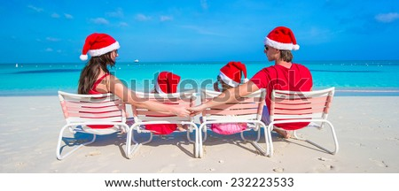 Happy family of four on beach in red Santa hats - stock photo
