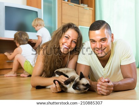 Happy family of four playing with kitten on the floor indoor - stock photo