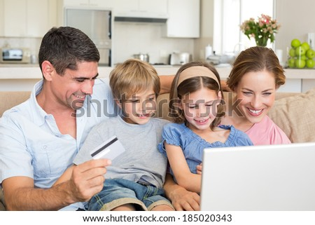 Happy family of four shopping online in house - stock photo