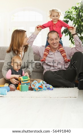 Happy family of four sitting at home on floor of living room, smiling girl sitting in daddy's neck. - stock photo
