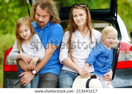 Happy family of four sitting in a car just before leaving for a car vacation - stock photo