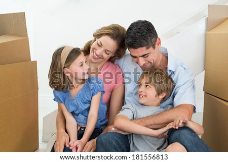 Happy family of four sitting in new house - stock photo