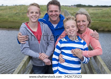 Happy Family of Four standing on a bridge over water. They have their arms around each other and are smiling at the camera.  - stock photo