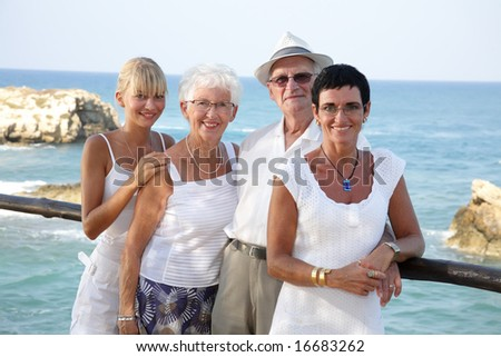 happy family of four standing outdoors (focus on grandparents) - stock photo