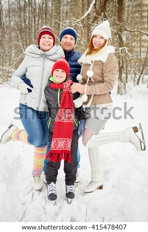 Happy family of four stands embracing on skates on ice pathway in winter park. - stock photo