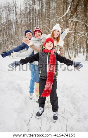 Happy family of four stands on skates on ice pathway in winter park spreading arms to sides. - stock photo
