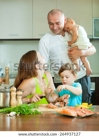 Happy family of four together in the kitchen prepares seafood - stock photo
