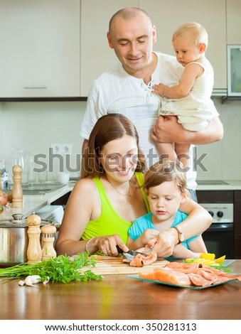 Happy family of four together on the big kitchen preparing seafood  - stock photo