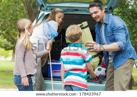 Happy family of four unloading car trunk while on picnic - stock photo