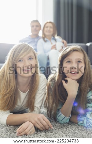 Happy family of four watching TV together at home - stock photo