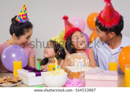 Happy family of four with cake and gifts at a birthday party - stock photo