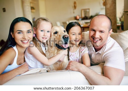 Happy family of four with dog looking at camera at home - stock photo