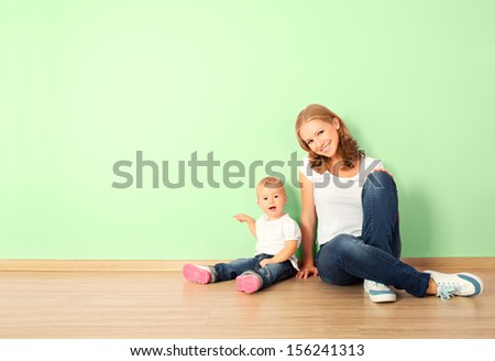 happy family of mother and child is a toddler sitting on the floor in an empty home wall in the room - stock photo