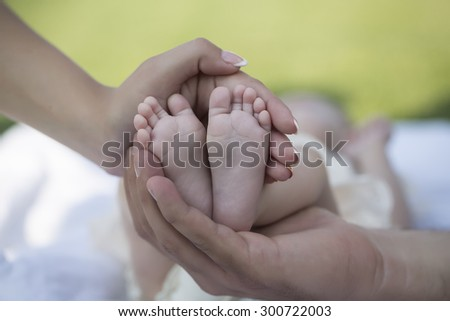 Happy family of mother and father touching bare feet with little toys and soft skin of small tiny baby with male and female hands outdoor closeup, hotizontal picture - stock photo