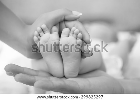 Happy family of mother and father touching bare feet with small toys and soft skin of little tiny child with male and female hands outdoor closeup black and white, hotizontal picture - stock photo