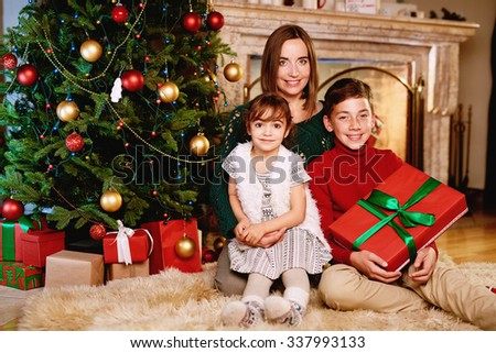 Happy family of mother and two kids looking at camera on Christmas evening at home - stock photo