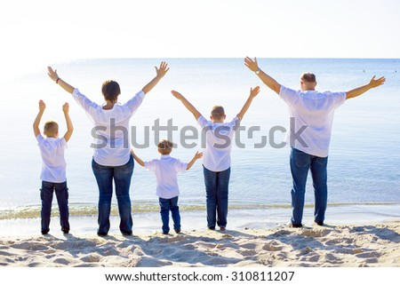 happy family of mother, father and three sons cheering on beach. Family enjoying the sunrise sunlight on seaside during summer vacations, family on vacations concept - stock photo
