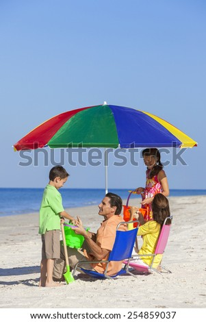 Happy family of mother & father, parents daughter & son children having fun in deckchairs under an umbrella on a sunny beach - stock photo